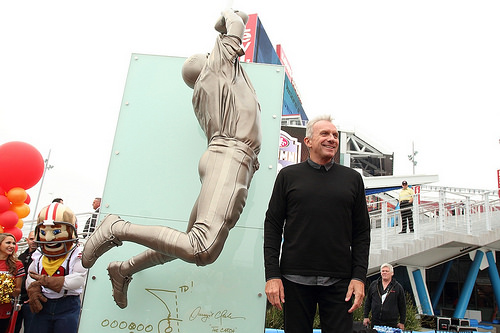 Joe Montana pose à côté de la statue de